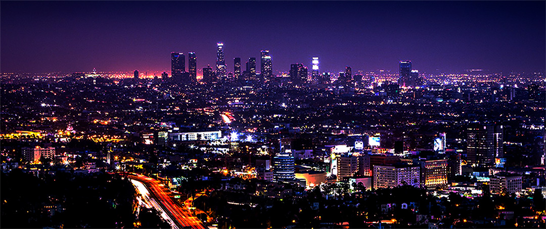 This is a deeply purple-colored photograph of downtown Los Angeles, CA, showing the dazzling colors and lights of the city after dark.